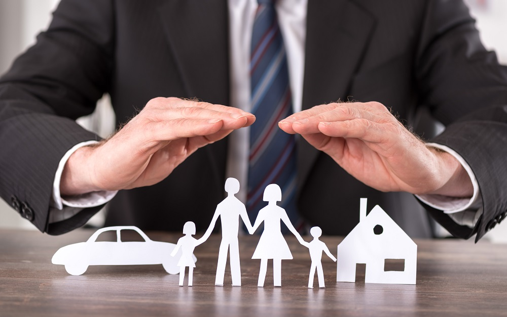 Concept of insurance with hands over a house, a car and a family